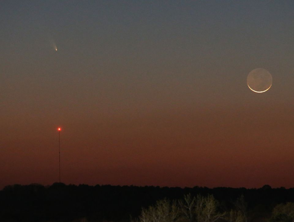 Comet Pan-STARRS is seen over the tower on the left as a 1 day waxing crescent Moon is seen setting in the Western sky on Tue