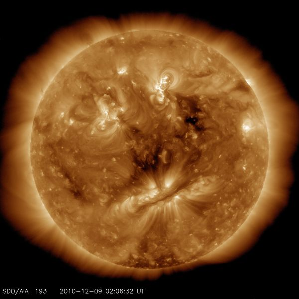 """This image shows features on the sun that look a bit like a human face. The """"eyes"""" show areas of hot material, the dark line"""