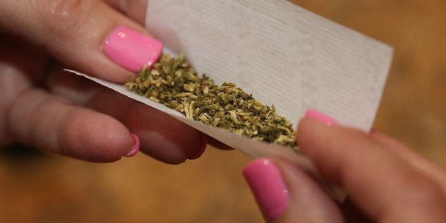 BETHPAGE, NY - AUGUST 30: A woman rolls a marijuana cigarette as photographed on August 30, 2014 in Bethpage,...