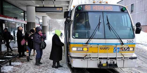 Passengers board a bus outside the MBTA subway stop in Davis Square in Somerville, Mass., Tuesday, Feb. 10, 2015. The third m