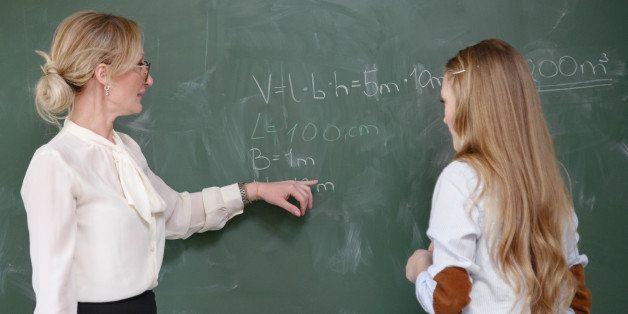 Nordic Education: teacher demonstrates a mathematical formula to a pupil at the chalk board.