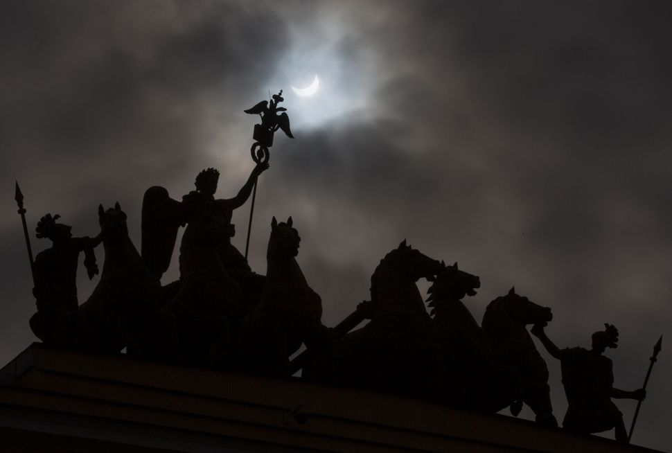 The moon blocks part of the sun during the solar eclipse as seen over a statue at one of the city landmarks, the General Staf