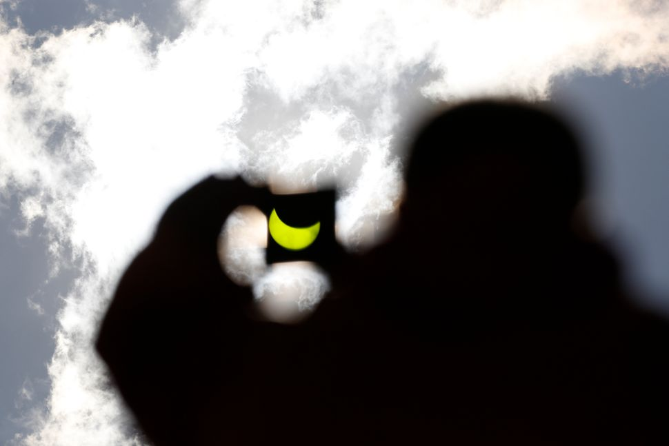 The solar eclipse is seen through a dark glass plate in Sarajevo, Bosnia.
