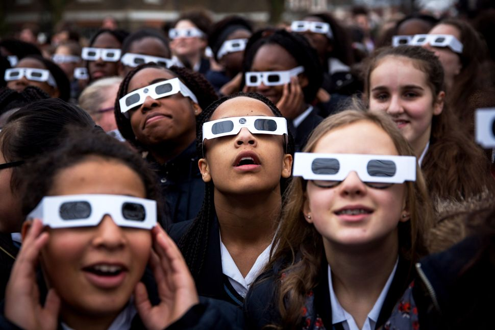 Students from Saint Ursula's Covent Secondary School in Greenwich pose for a photograph wearing protective glasses at the Roy