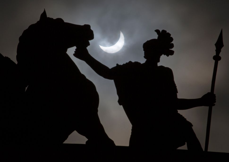 The moon blocks part of the sun during the solar eclipse as seen over the city landmarks statue in St.Petersburg, Russia.