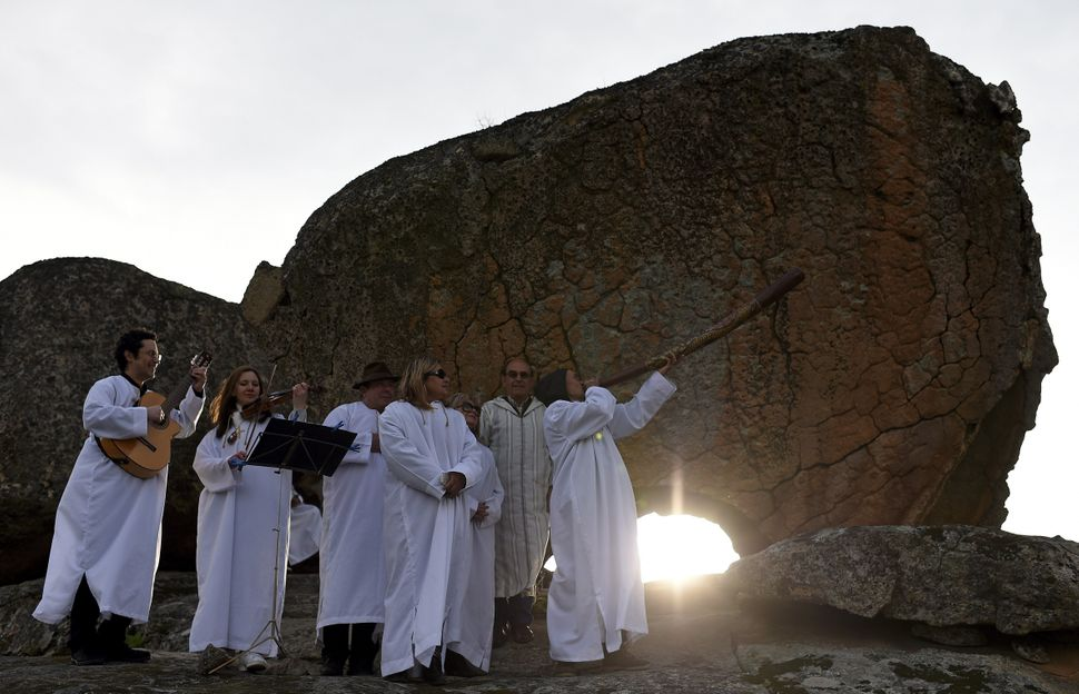 Performers play instruments at sunrise near a prehistoric stone shrine aligned to the Spring Equinox in Chas, northeast Portu
