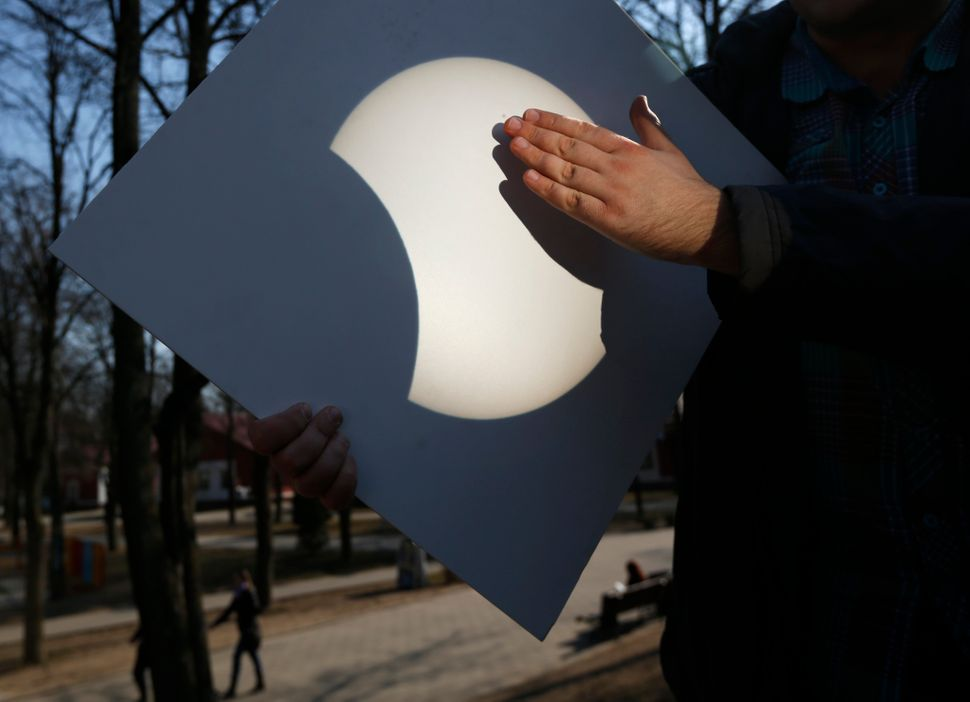 The solar eclipse is reflected onto a white piece of cardboard during a viewing party in Minsk, Belarus.
