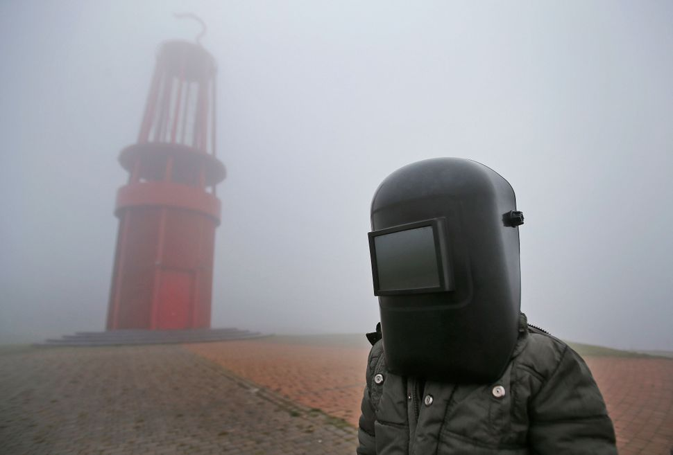 A young boy wearing his father's welding mask to watch the solar eclipse in Duisburg, Germany.