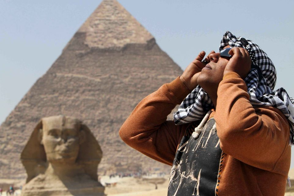 A skywatcher uses special glasses to view the solar eclipse as people gather near the Sphinx at the Giza Pyramids on the outs