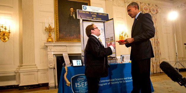 "Harry Paul, 18, of Port Washington, N.Y., left, shows President Barack Obama his ""growing spine implant"" during Obama's tour"