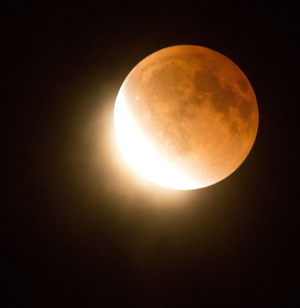 The moon moves out of  a lunar eclipse over southern California as seen from Korea town, west of downtown Los Angeles early o