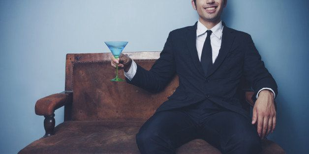 Smiling young businessman is sitting on a vintage style sofa with a martini glass in his hand
