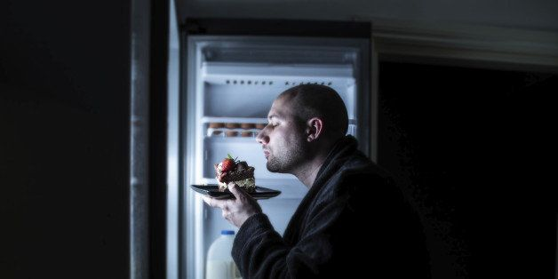 a bald man in his dressing gown sniffing and savouring a slab of cake left in the