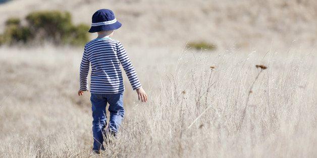 little boy enjoying beautiful weather alone outdoors
