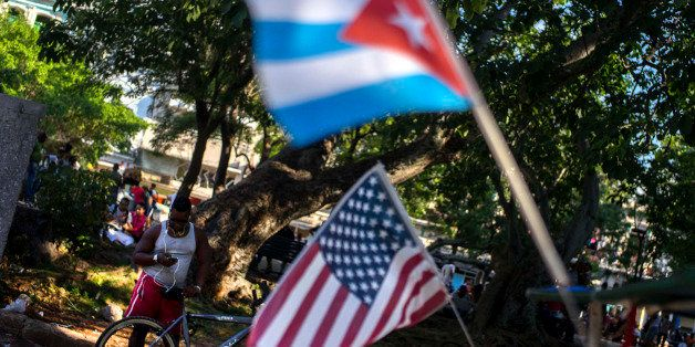 A man chats on his mobile phone, close to a pair of Cuban and US flags strapped to a bicycle taxi, at a public Wi-Fi hotspot