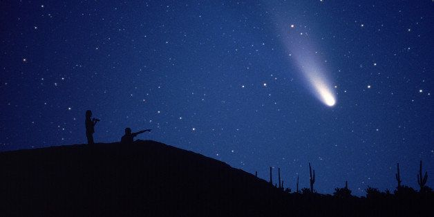 Comet Hale-Bopp is viewed by a couple on a hillside overlooking the Arizona desert.