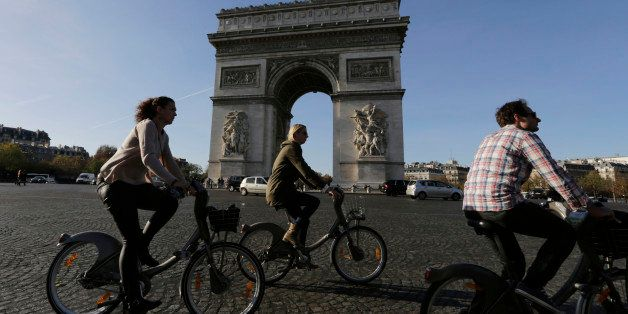 Tourists enjoy bicycle tours pass the Arch of Triumph in the Champs Elysees district of Paris, France, Sunday, Nov. 15, 2015.