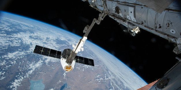 The Canadarm 2 reaches out to capture the SpaceX Dragon cargo spacecraft and prepare it to be pulled into its port on the Int