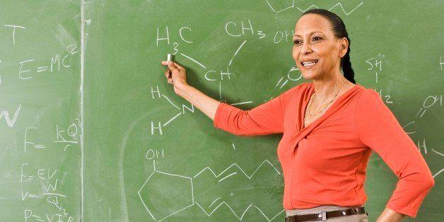 Science teacher by chalkboard