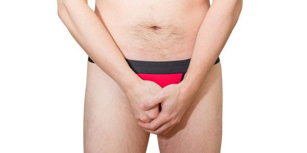Adult man in black&red underwear holding/hiding/protecting his penis, isolated on white background.