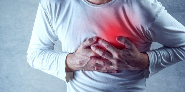 Severe heartache, man suffering from chest pain, having heart attack or painful cramps, pressing on chest with painful expres