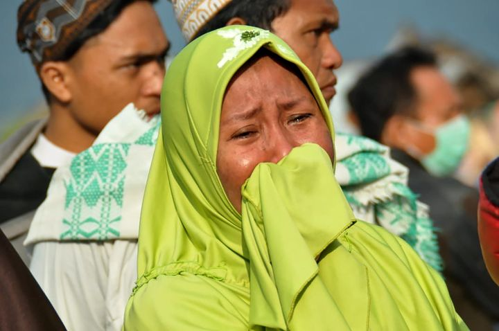 A woman cries as people look at the damages after an earthquake and a tsunami hit Palu, on Sulawesi island on September 29, 2