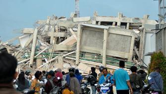 Residents gather to look at a collapsed building after an earthquake and tsunami hit Palu on Sulawesi island on September 29, 2018. - Nearly 400 people were killed when a powerful quake sent a tsunami barrelling into the Indonesian island of Sulawesi, officials said on September 29, as hospitals struggled to cope with hundreds of injured and rescuers scrambled to reach the stricken region. (Photo by MUHAMMAD RIFKI / AFP)        (Photo credit should read MUHAMMAD RIFKI/AFP/Getty Images)