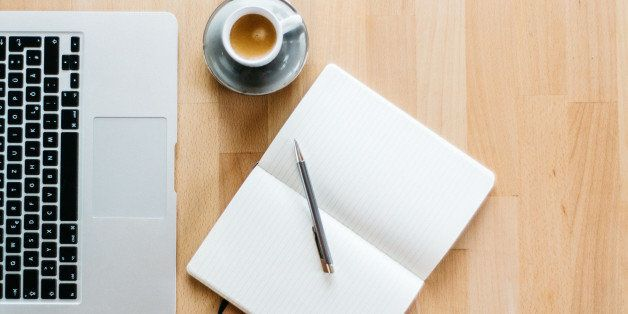 A photo of a workspace with a Laptop, an espresso and a notebook with a pen. The photo is taken from directly above and the w