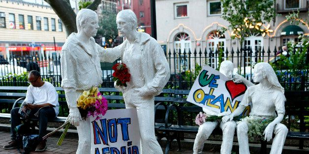 NEW YORK, NY - JUNE 12: Tribute signs are placed on statues depicting homosexual couples in a park near the Stonewall Inn whe