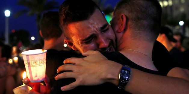 People embrace during a candlelight vigil at a memorial service for the victims of the shooting at the Pulse gay night club i