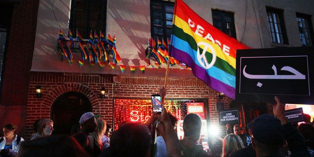 NEW YORK, NY - JUNE 12: Mourners gather outside of the iconic New York City gay and lesbian bar the Stonewall Inn to light ca