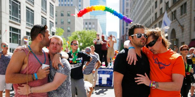BOSTON - JUNE 12: From left, Chris Hemming, of NYC, kisses Tristan Davison, also of NYC, as Jeffery Greamo, of Boston, embrac