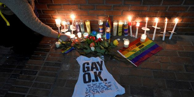 A woman places a candle at a make-shift memorial for the victims of the mass shooting at Orlando's Pulse nightclub, in Boston