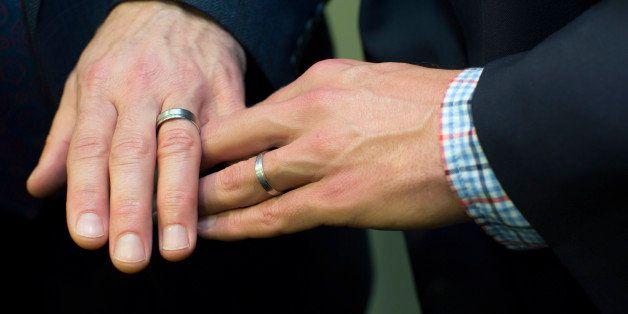 Men's hands together showing wedding rings
