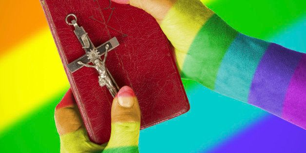 Old hands (woman) holding a very old bible, rainbow flag patternHand (woman) holding a very old bible, isolated on white, rai