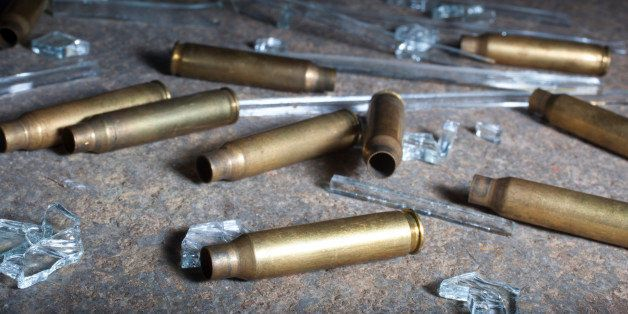 Rifle brass mixed with broken glass on a nighttime concrete slab
