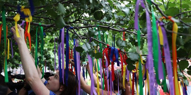 NEW YORK, NY - JUNE 16:  People tie ribbons on the Survivor Tree at the National September 11 Memorial & Museum in honor of t