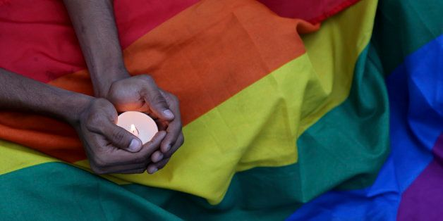 A participant holds a candle as activists of India's LGBT (Lesbians Gays Bisexuals Transgenders) community and their suppor