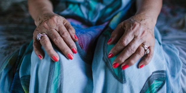 Close up of hands of older woman resting on knees