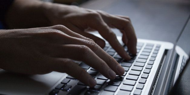 The hands of a young adult typing on the keyboard of a silver colored laptop. Backlit with high contrast.