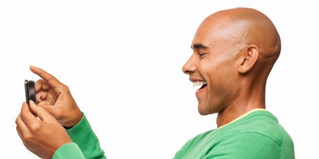 Side view of happy African American man taking self portrait with cell phone. Horizontal shot. Isolated on white.