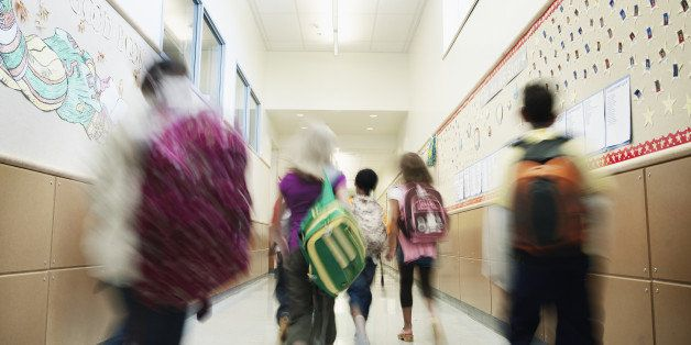Young students with backpacks walking down hallway of elementary school