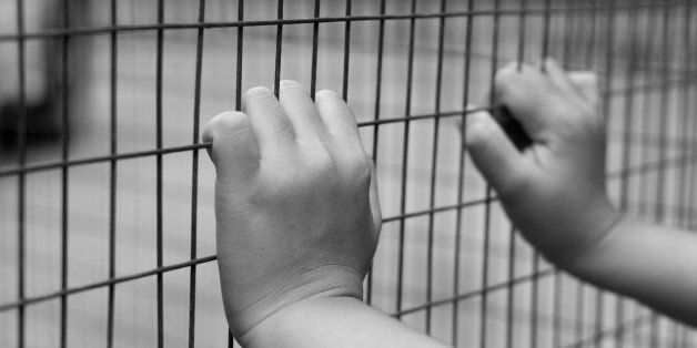 Hand of prisoner grabbed the metal  fence in black and white