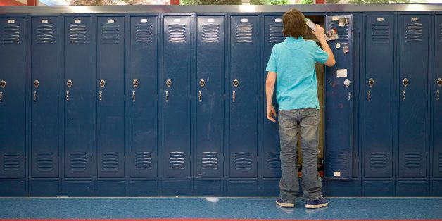 Teenage boy (13-15) putting books in locker, rear view