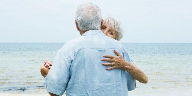 Senior couple dancing on sidewalk overlooking ocean, waist up