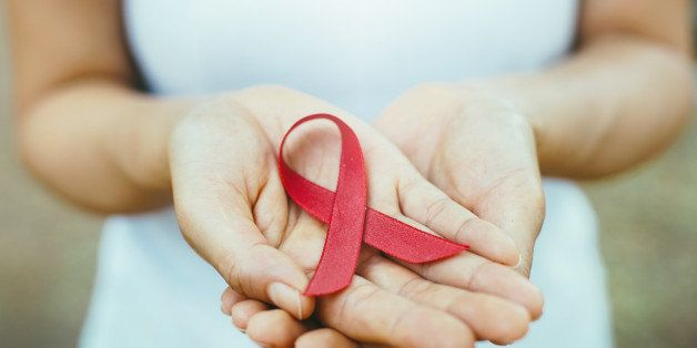 red aids ribbon in hand. soft focus on ribbon