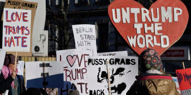 Demonstrators protesting against US president-elect Donald Trump display placards during a so called 'Pussy Grabs Back' demon