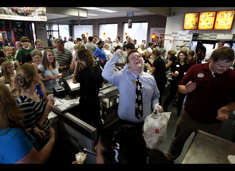 Chick-fil-A team member Dakota Bibbs, center, cheers as customers aid in his search for the owner of an order ready for pick-