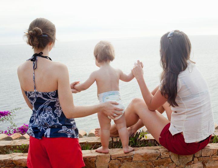women holding baby's hand