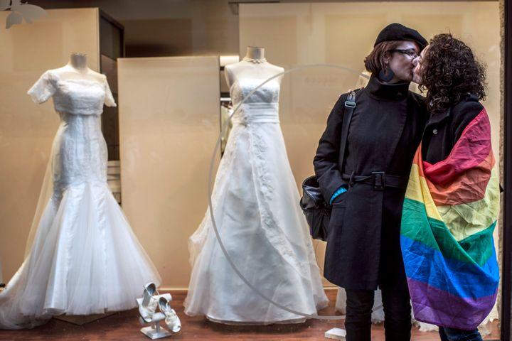 Two women, one wrapped in a rainbow flag, kiss in front of a wedding shop during a demonstration to support gay marriage and